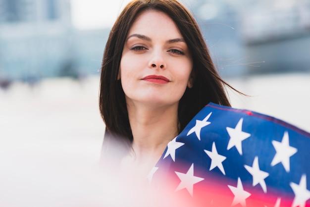 Frau, die kamera mit weißen sternen der amerikanischen flagge betrachtet