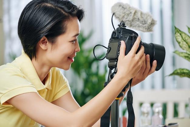 Frau, die kameraeigenschaften einstellt