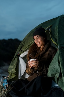 Frau, die kampiert und eine tasse tee hält