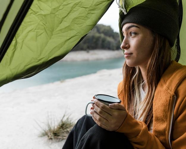 Frau, die kampiert und eine tasse tee hat