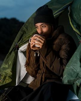 Frau, die kampiert und eine tasse tee trinkt