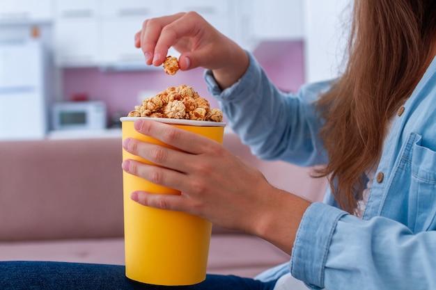 Frau, die karamellpopcorn isst, während sie zu hause fernsieht