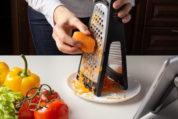 Frau, die karotten reibt und virtuelle kulinarische klasse beobachtet. online-kochkurs