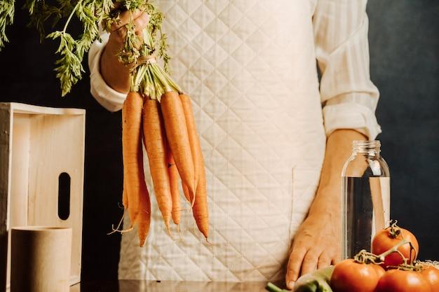 Frau, die karotten und gemüse über einem tisch mit wasser nahe ihrem gesunden lebensmittelkonzept mit kopienraum hält