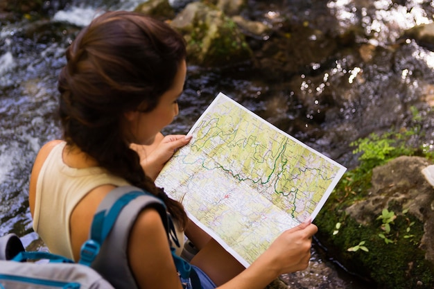 Frau, die karte benutzt, um natur zu erforschen