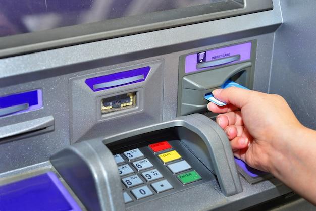 Frau, die karte hält, mit geldautomat