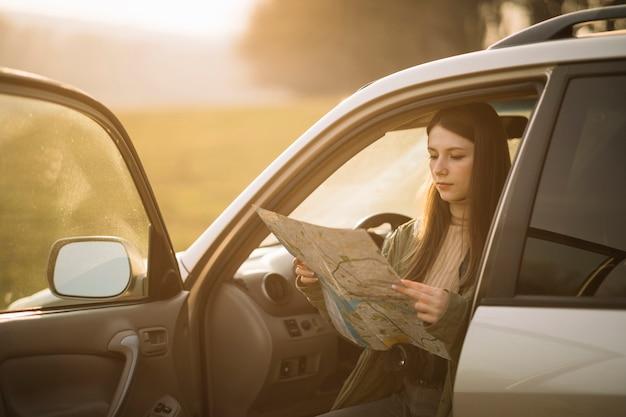 Frau, die karte im auto hält