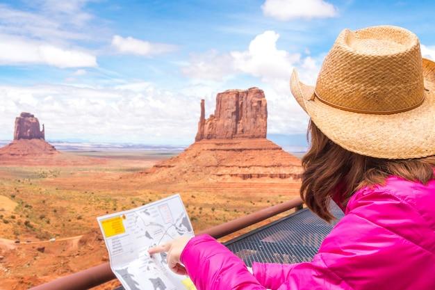 Frau, die karte im monument-tal mit rotem felsenüberblick in arizona usa sitzt und betrachtet