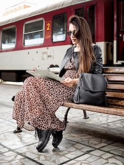 Frau, die karte liest, während auf zug wartet