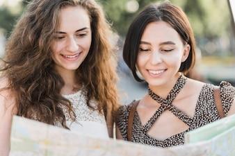 Frau, die Karte und das Lächeln betrachtet