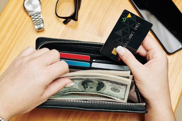 Frau, die karte und geld in geldbörse legt