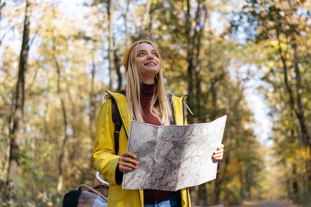 Frau, die karte verwendet, um im herbstwald zu navigieren. aktiver lebensstil, reisekonzept