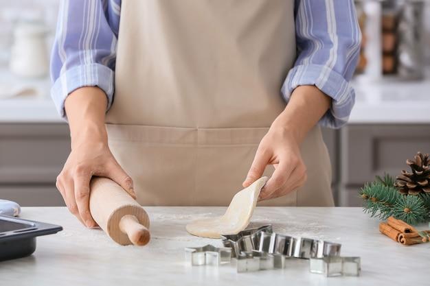 Frau, die kekse auf tisch in der küche macht