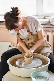 Frau, die keramische tonwaren auf rad macht