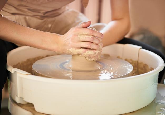 Frau, die keramische tonwaren auf rad, schaffung der keramik macht.