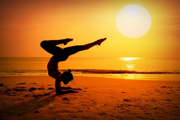 Frau, die kiefer auf dem strand bei sonnenuntergang