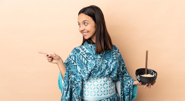 Frau, die kimono trägt und eine schüssel voll nudeln hält, die zur seite zeigen, um ein produkt zu präsentieren, während eine schüssel nudeln mit stäbchen hält
