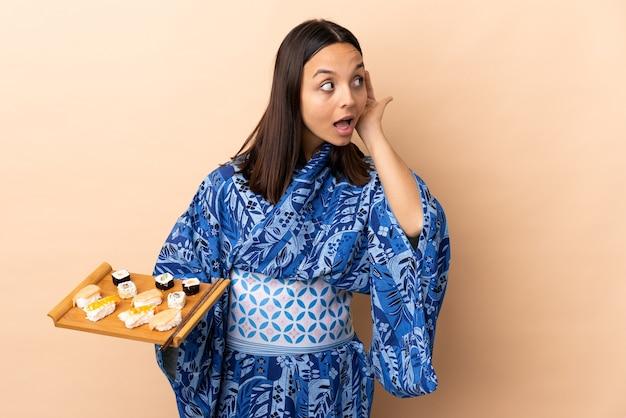 Frau, die kimono trägt und sushi hält