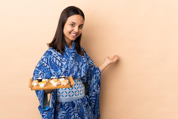 Frau, die kimono trägt und sushi über isolierter wand hält, die hände zur seite für einladung zum kommen ausdehnt