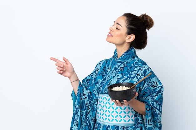 Frau, die kimono über isolierter weißer wand trägt, die zur seite zeigt, um ein produkt zu präsentieren, während sie eine schüssel nudeln mit stäbchen hält
