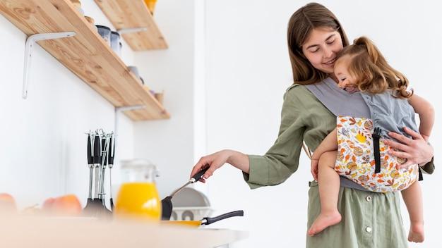 Frau, die kind beim kochen hält