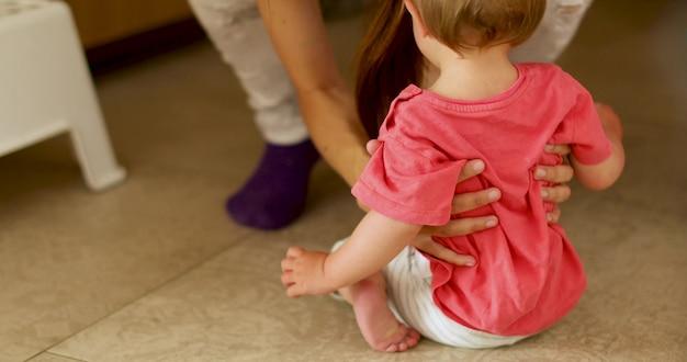 Frau, die kind vom boden aufhebt