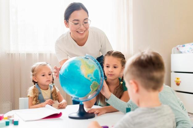 Frau, die kinder geographie lehrt