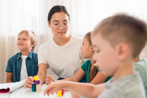 Frau, die kinder lehrt, wie man mit buntem spiel spielt