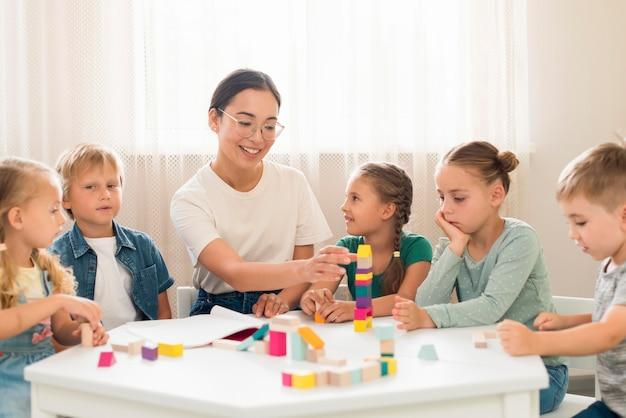 Frau, die kinder lehrt, wie man mit buntem spiel während des unterrichts spielt