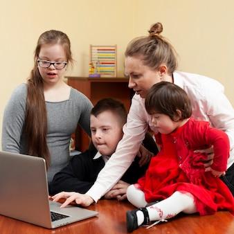 Frau, die kinder mit down-syndrom etwas auf laptop zeigt