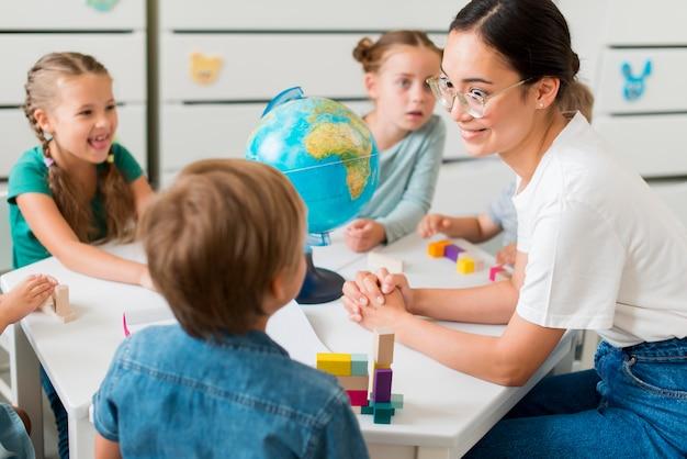 Frau, die kindern geographie lehrt