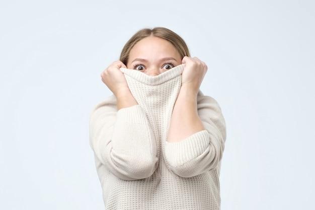 Frau, die kindisches verstecktes gesicht in ihren kleidern ist