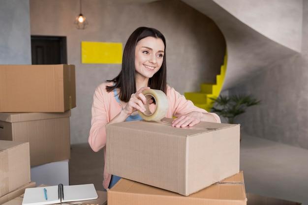 Frau, die kisten packt, um zu liefern