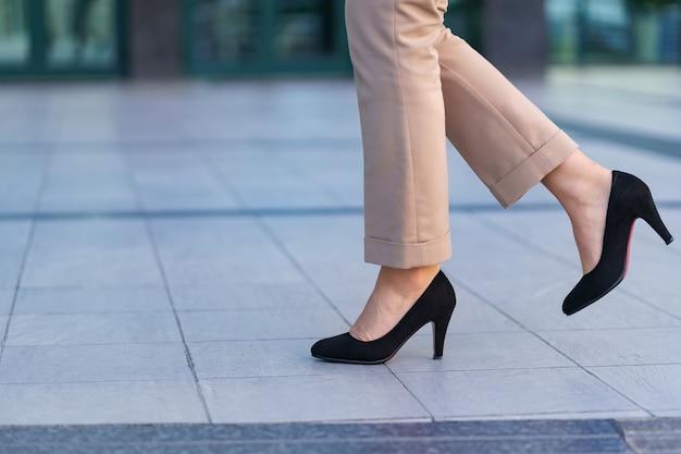 Frau, die klassische schwarze schuhe mit hohen absätzen trägt. modell posiert auf der straße. elegantes outfit. nahansicht.