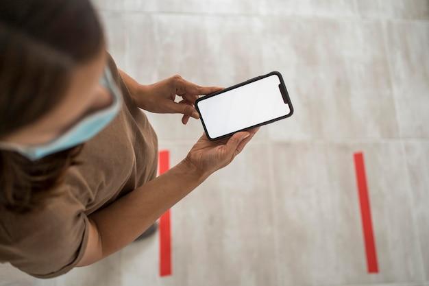 Frau, die klebeband auf den boden für soziale distanzierung beim verwenden des smartphones legt