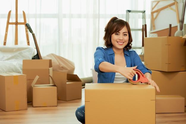 Frau, die kleber am paketkasten lächelt an der kamera sitzt auf dem boden haftet