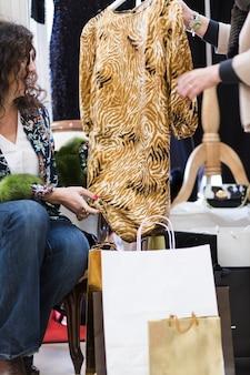 Frau, die kleid im shop betrachtet