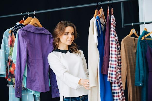 Frau, die kleider auf kleiderschiene betrachtet