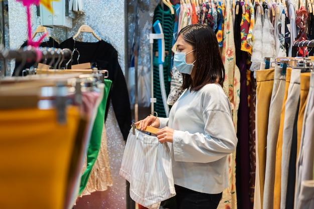 Frau, die kleidung am einkaufszentrum wählt und medizinische maske zur verhinderung von coronavirus trägt