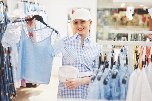 Frau, die kleidung einkauft. käufer, der kleidung drinnen im laden betrachtet. schönes glückliches lächelndes asiatisches kaukasisches weibliches modell