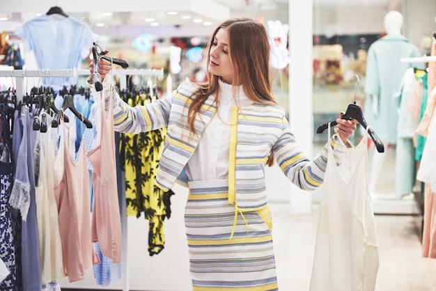 Frau, die kleidung einkauft. käufer, der kleidung drinnen im laden betrachtet. schönes glückliches lächelndes kaukasisches weibliches modell