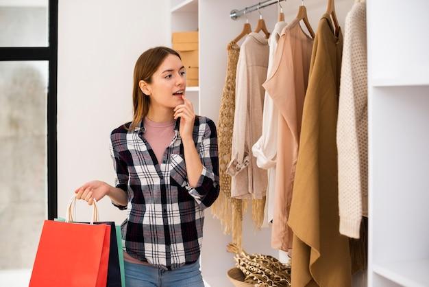 Frau, die kleidung für eine garderobe wählt