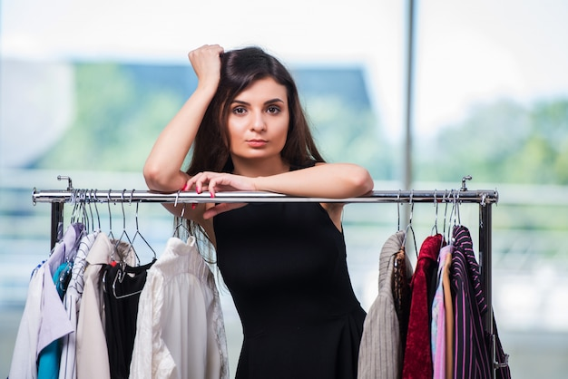 Frau, die kleidung im shop wählt