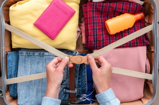 Frau, die kleidung in einen koffer für eine neue reise und reisen packt. gepäck für urlaub und ferien. draufsicht