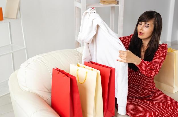Frau, die kleidung prüft, die sie beim verkaufeinkauf erhielt