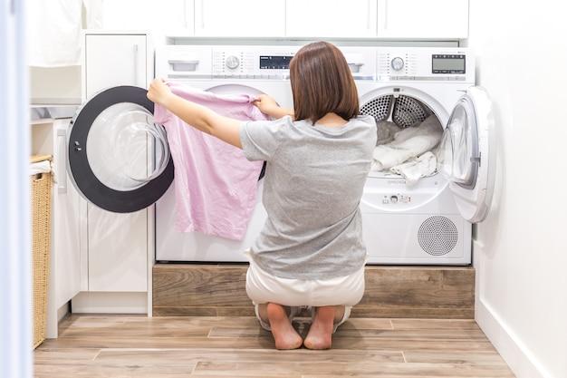 Frau, die kleidung zur waschmaschine für wäsche setzt
