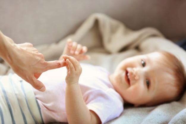 Frau, die kleine babyhand hält