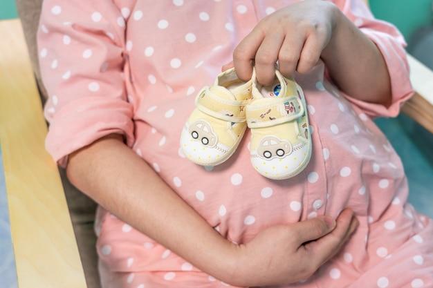 Frau, die kleine schuhe für das ungeborene baby im bauch der schwangeren frau hält.