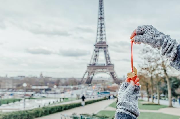 Frau, die kleinen keramikvogel auf dem eiffelturm in paris, frankreich hält