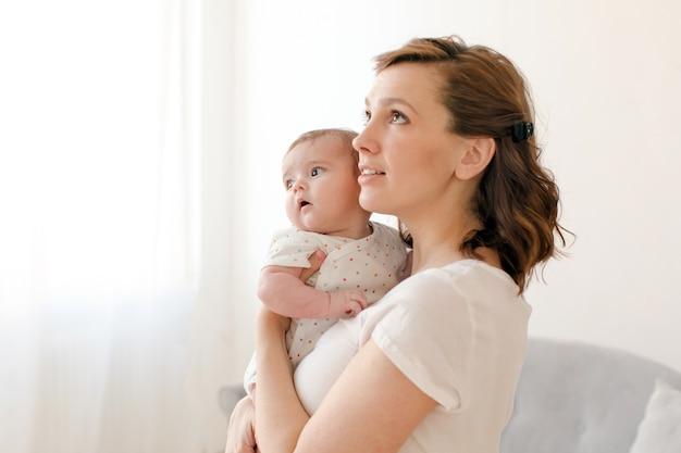Frau, die kleines baby auf händen anhält